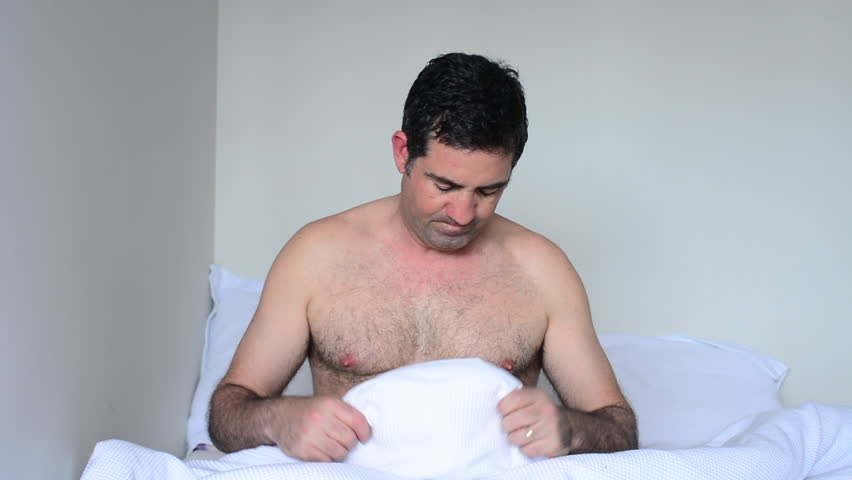 Upset man in his forties (40s) in bed looking down at his penis under white covers sheet in bedroom. Concept photo of male sexuality and man sex and relationship problem concept (Slider motion)