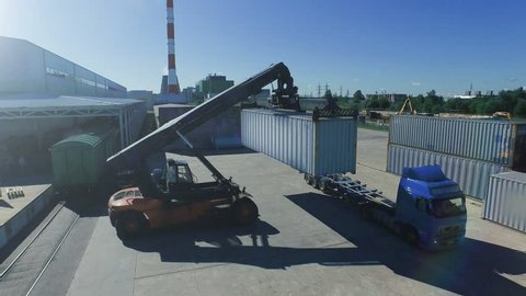 Container Handler is Loading Container onto Truck in Logistic Center. Aerial Shot.
