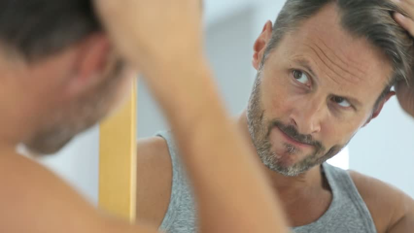 Middle-aged man concerned by hair loss | Shutterstock HD Video #12375485