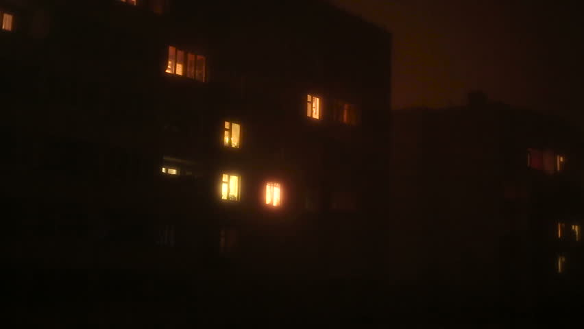 Light in the windows of a multistory building at night. | Shutterstock HD Video #12385490
