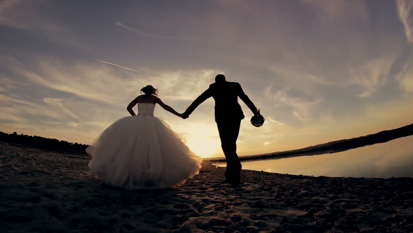 The bride and groom running  on the beach at sunset in the sand. Rear view.