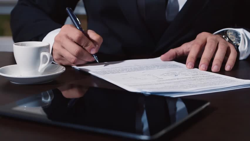 Man's hand in a business suit signs documents | Shutterstock HD Video #12411560
