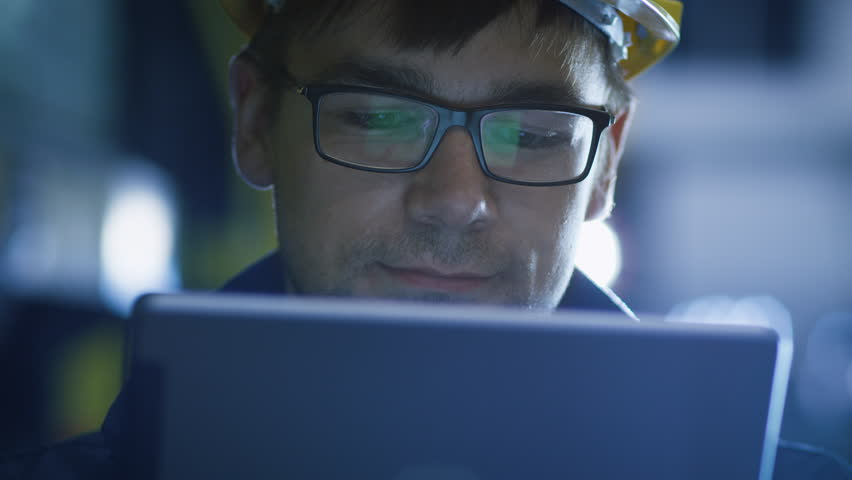 Technician in Glasses and Hard Hat Using Tablet in Industrial Environment. Reflections of Screen Glasses. Shot on RED Cinema Camera in 4K (UHD).