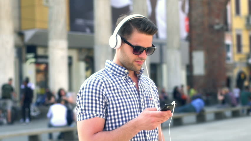 Man listening music on the square in the city, steadycam shot