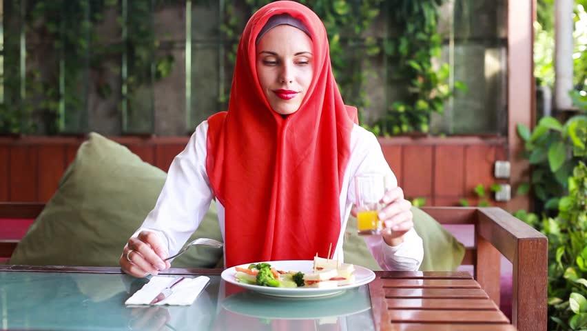 Muslim woman enjoying halal food and juice