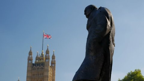 Statue of Churchill in Parliament Square London with the Victoria Tower and Union Flag in the background