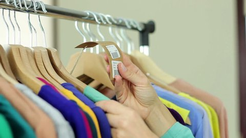 Young woman looking at price tag in clothing store, close up