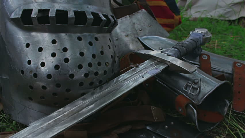 Medieval plate armor with a sword, chain mail and helmet lying on the grass. | Shutterstock HD Video #12500210