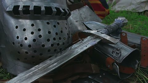 Medieval plate armor with a sword, chain mail and helmet lying on the grass.