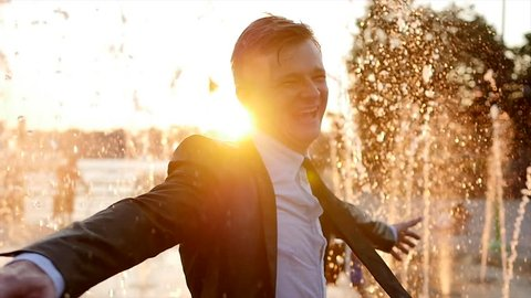 one young caucasian business man dancing outdoors running trough water fountain at sunset. successful happiness career background