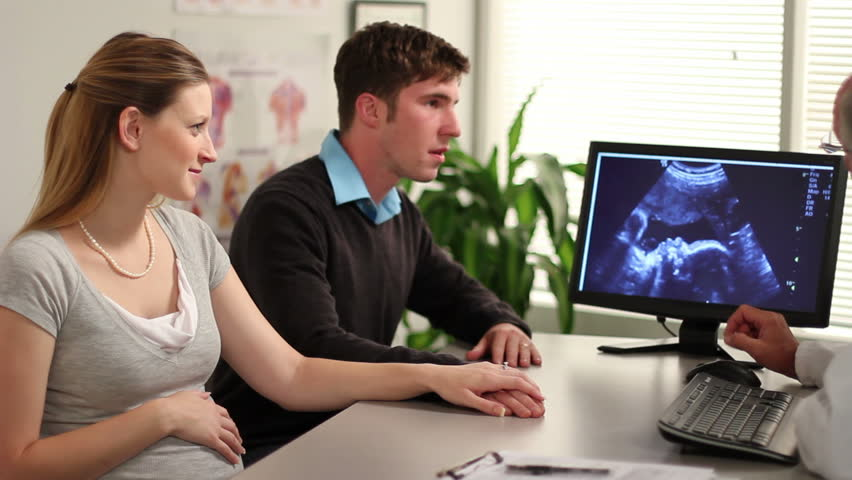 A young couple and a doctor look at an ultrasound