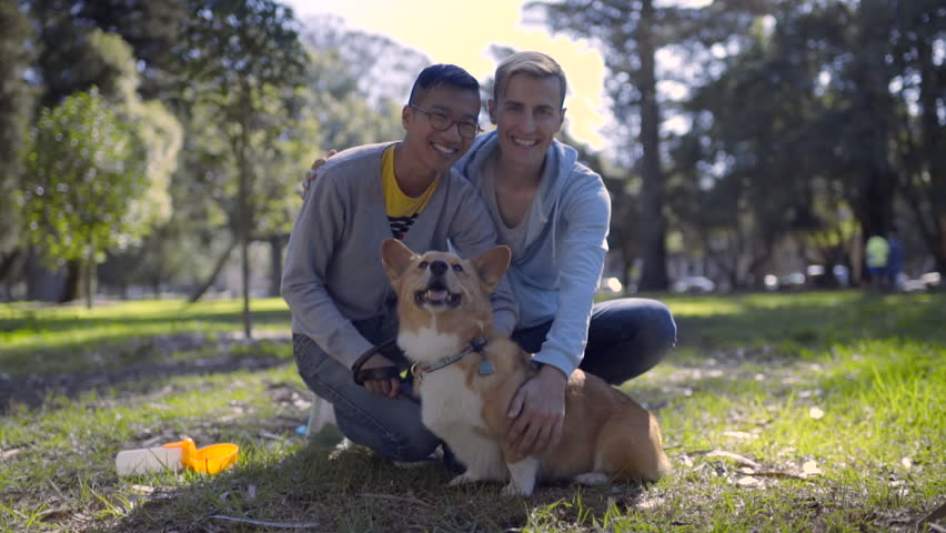 Happy Gay Couple Pose With Their Pembroke Welsh Corgi Dog In Park