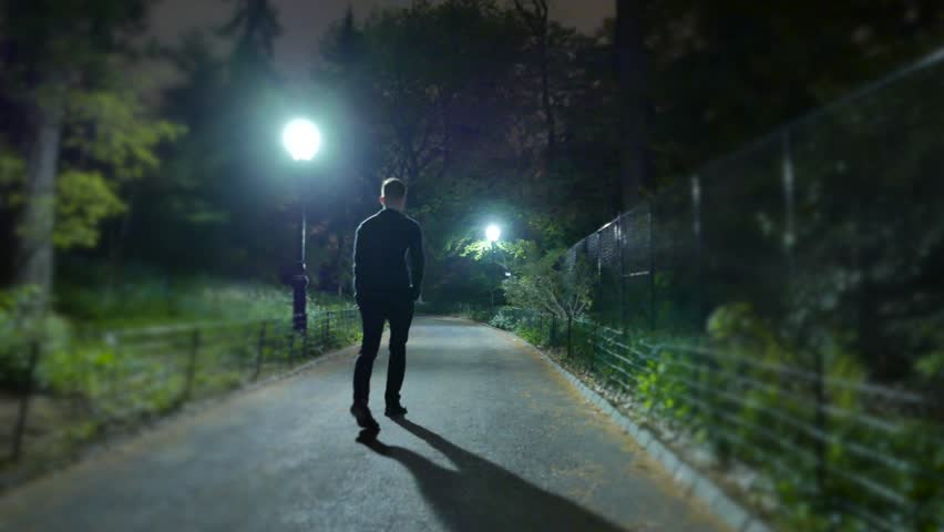 Man walking alone at night in the park. shadow silhouette of person. spooky night scenery background  | Shutterstock HD Video #12548720