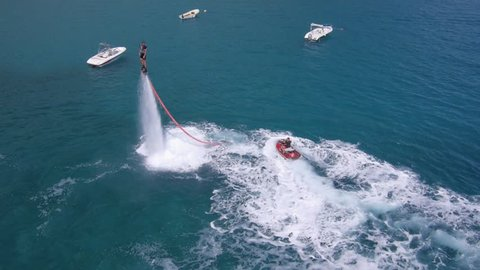 Aerial view on man enjoying water jet pack flyboard at the sea.