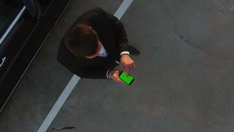 Zoom Out from Businessman Green Screen Phone to Bird eye Phone City with Traffic