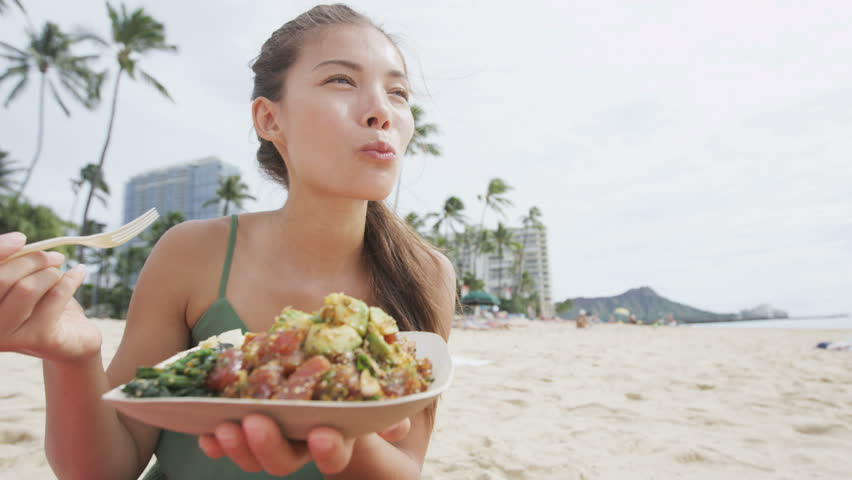 Young woman eating traditional Hawaiian food at beach. Beautiful female is holding poke salad plate with raw marinated tuna fish. Tourist is representing her healthy lifestyle.