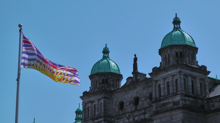 The flag of British Columbia, Canada waves in front of the parliament building in Victoria.