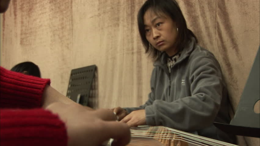Beijing, China - February 2008: Chinese music teacher and children playing the guzheng, a traditional Chinese string instrument, in class. Beijing, China.