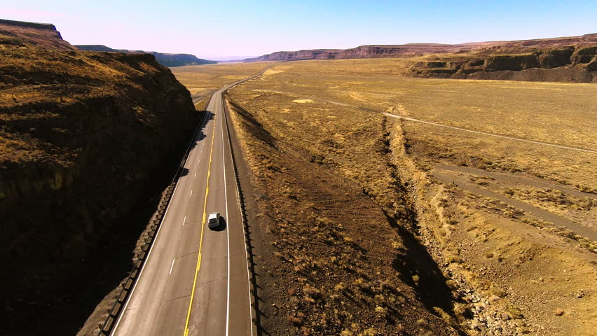 Aerial Footage Of Highway in a Canyon. Hot and humid loan road through the countryside. One car driving through.