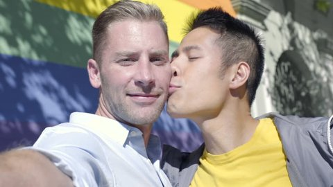 Attractive Gay Couple Kiss On Cheek And Pose For Selfie In Front Of Gay Pride Rainbow Wall
