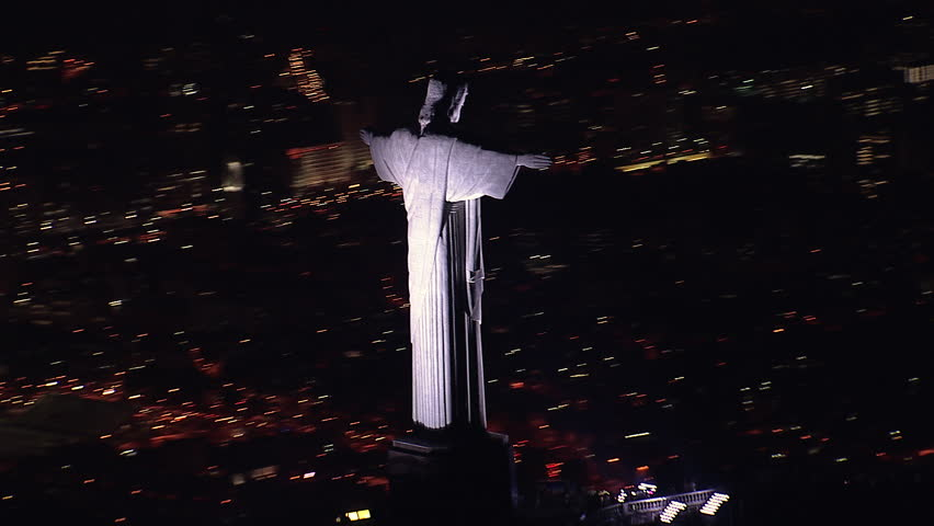 RIO DE JANEIRO, BRAZIL - OCTOBER 2015: Aerial closeup view of illuminated Christ the Redeemer Statue at Night, Rio de Janeiro, Brazil. View of Christ overlooking Rio with background city lights.