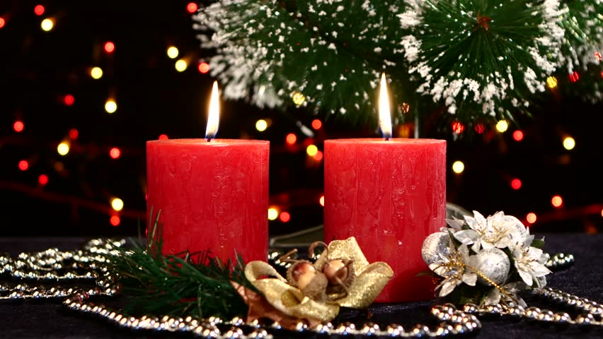 Two big red candles with christmas decorations and tree on black background, bokeh, light, garland, rotation