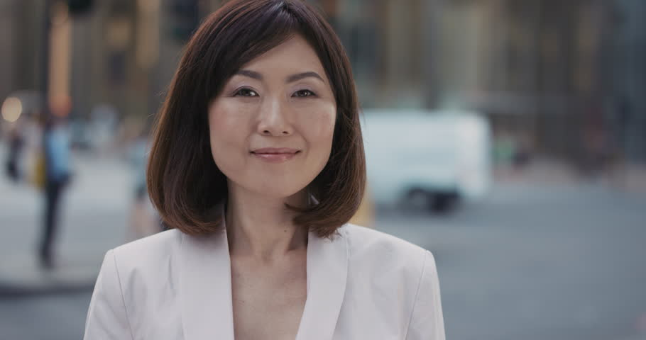 Slow Motion Portrait of beautiful Japanese businesswoman smiling in city real people series