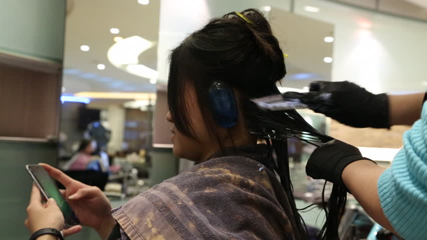 Asian Beautiful Woman Playing With Smartphone In Hair Salon While ...