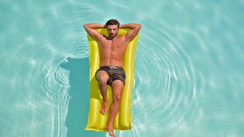 man relaxing on the air bed in the swimming pool. concept about vacation and free time