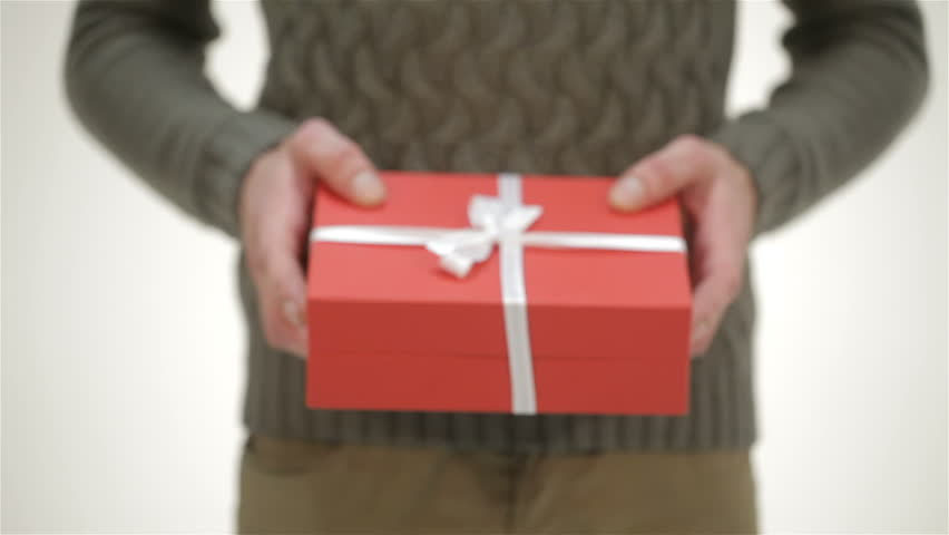 Close up the male gives a gift. Young attractive couple in Santa hat, cozy sweaters, smiling, congratulate each other a Happy New Year, Merry Christmas, Happy Valentine's Day, presents gifts, laughing | Shutterstock HD Video #12698027