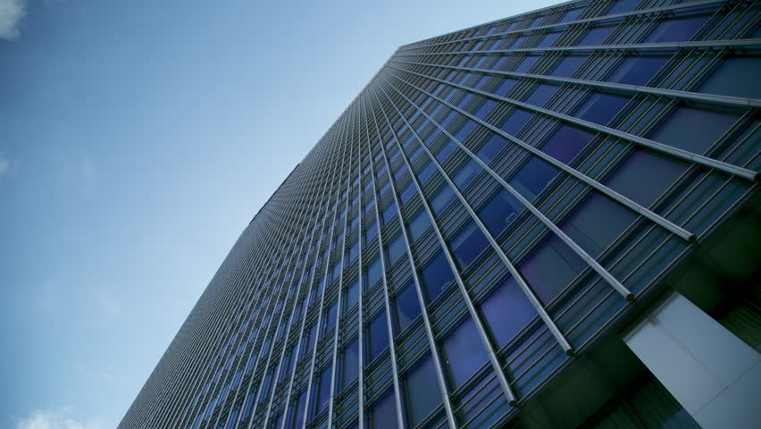 Stunning Low Angle Vertical Skyscraper Office Building With Gleaming Metal Structure Reflecting the Blue Sky and Moving Clouds Overhead 4K UltraHD Timelapse #12720350