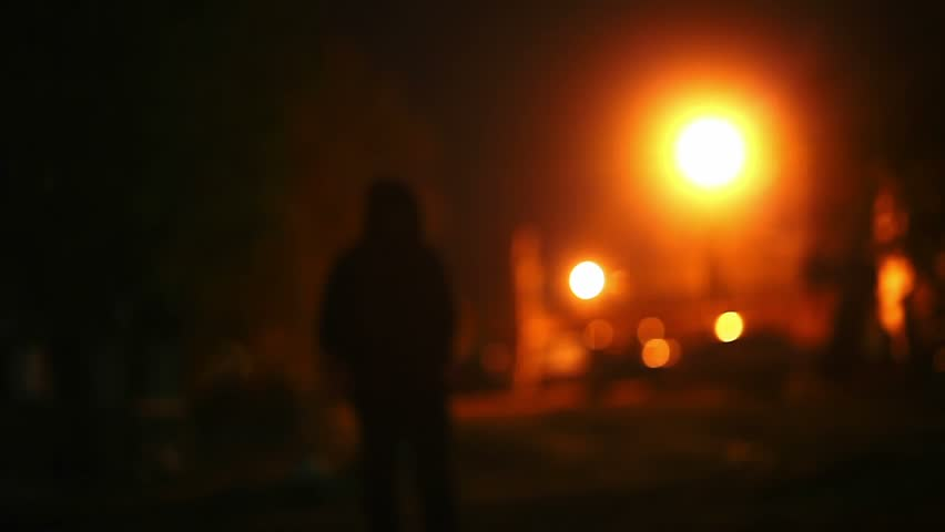 silhouette  of man in the hood is a night light lantern thief offender