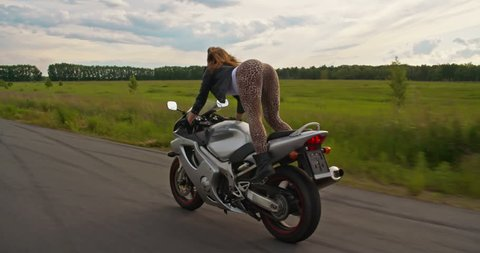 Sexy woman biker shaking her hips and riding motorcycle at the same time