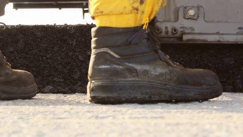 Tracked paver laying fresh asphalt pavement
