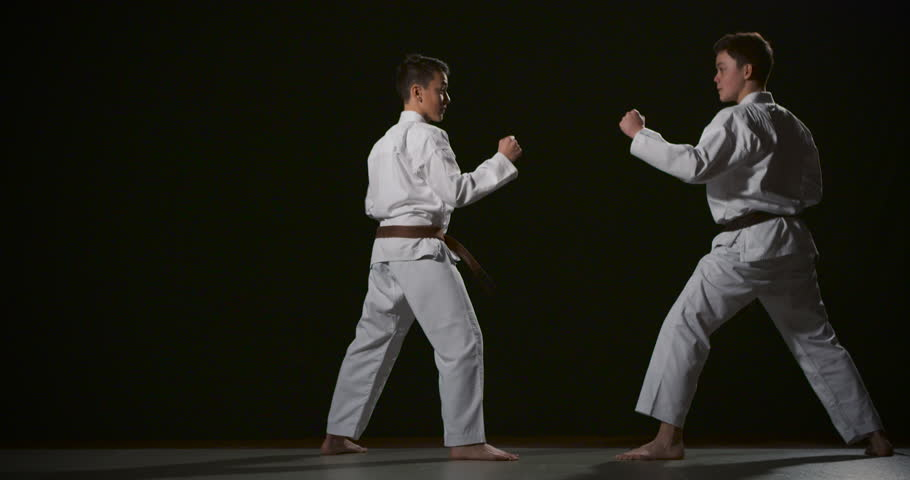 Two boys performing Ju-jitsu duo system competition exercise slow motion 50fps on black background