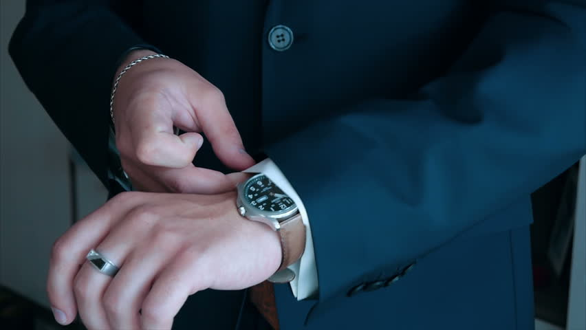 the groom is going to the wedding ceremony dress watches and straightens his shirt in a suit, emotions slow motion, stylish fashionable bride groom wedding charges an elegance bride