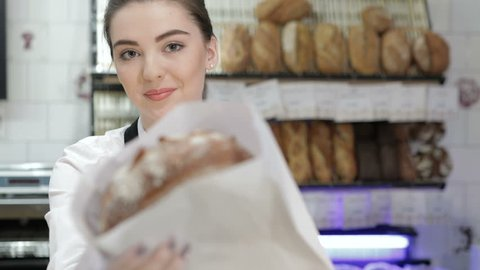 Portrait of a seller giving the fresh baked bread in a paper bag. Young smiling baker inside the coffee shop or bakery offers fresh breads, pastries, muffins, macaroon, muffins. The assortment of the