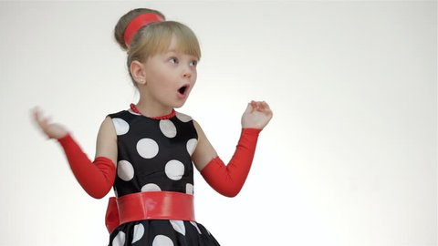 Kid girl surprised looking at copy space. Kid girl posing in studio isolated on white background. The girl dressed in the summer red polka dot sleeves and arm warmers, hair ribbon. She is surprised