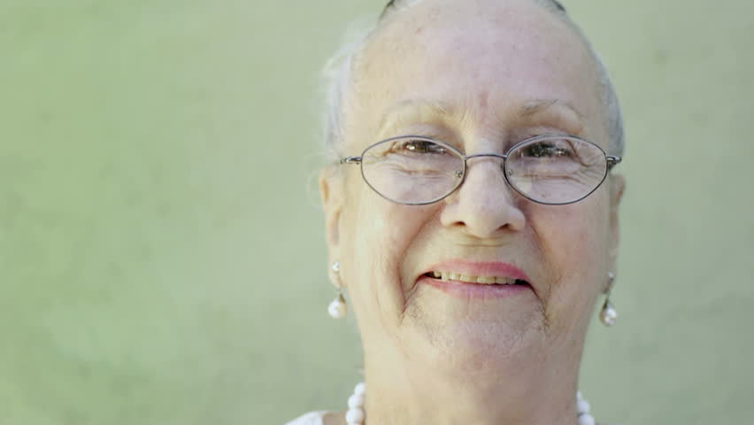 portrait of senior caucasian woman looking at camera against green wall and smiling