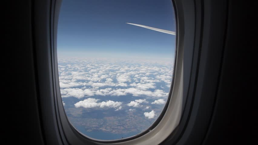Clouds seen through the window of jet airplane. Airplane flies above the weather