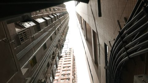 POV walk look up, low angle shot between tall buildings rising high. Move along narrow passage urban block, typical apartments and business towers at Causeway Bay area, Wan Chai district of Hong Kong.