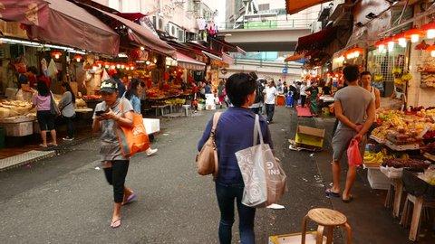 HONG KONG - MARCH 31, 2015: Unidentified chinese people walk through Bowrington wet market, Wan Chai road at Wan Chai district of Hong Kong Island. Fresh fruits and raw seafood and fish stalls