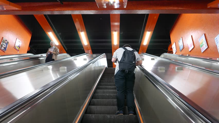 HONG KONG   MARCH 31, 2015: Unidentified Boy Stand At Escalator Moving Up,