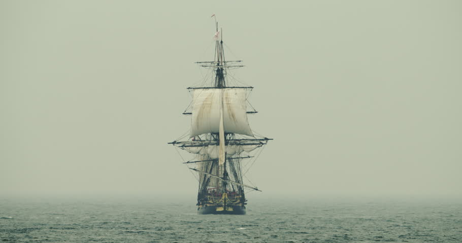 Historical tall ship schooner sails on the high seas in misty fog. Navy.