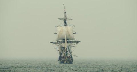 Historical tall ship schooner sails on the high seas in misty fog. Navy.