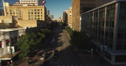 The camera flies north over Congress Avenue in Austin, Texas as it gains altitude to showcase the state capitol building.