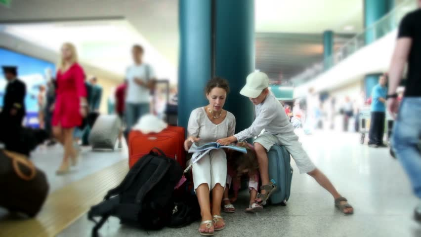 Mother and her two kids boy and girl sit in airport and reading book, their luggage stand near
