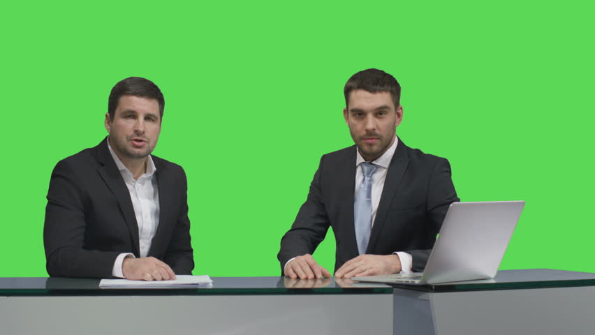 Two media broadcasters are sitting at a table with a laptop and talking on a mock-up green screen in the background. Shot on RED Cinema Camera in 4K (UHD). | Shutterstock HD Video #12942740