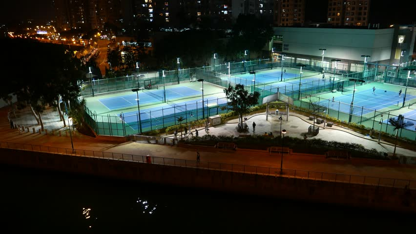Tennis courts illuminated in night, general pan view, dark city area. Aberdeen Tennis And Squash Centre Tennis Courts, Hong Kong outskirts. Playground area as seen from Ap Lie Chau bridge, night time | Shutterstock HD Video #12944450
