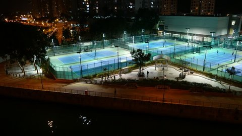Tennis courts illuminated in night, general pan view, dark city area. Aberdeen Tennis And Squash Centre Tennis Courts, Hong Kong outskirts. Playground area as seen from Ap Lie Chau bridge, night time